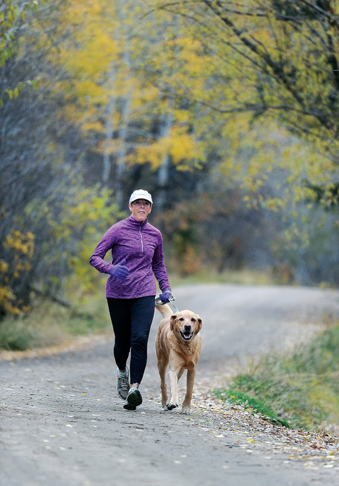 Diane Carter and her running partner, Oscar, who belongs to a neighbor, take a training run along Spring Creek Trail on Wednesday morning. Carter has run in a marathon every year since 2000 and will compete in this year's New York Marathon on Nov. 3. Carter will run in honor of Matt Dudley and plans to donate the money to leukemia research. Dudley, who grew up in Steamboat Springs, was diagnosed in March with acute myelogenous leukemia, a cancer of the blood and bone marrow.