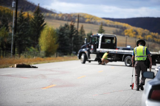 Colorado State Patrol Trooper Sampson takes measurements while investigating a fatal crash on Colorado Highway 131 near mile marker 61 between Steamboat Springs and Oak Creek. The motorcycle driver lost control after hitting a deer.