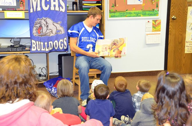 "Moffat County High School Joe Camilletti reads ""How Do Dinosaurs Say I'm Mad?"" to children during Thursday morning story time at the Craig branch of the Moffat County Libraries. Numerous other MCHS students also read to elementary students as well the Friday of Homecoming week."