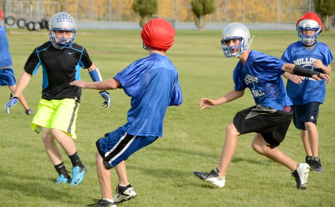 Moffat County players Brayden Peterson (left, in black) and Kearn Gerber contain an outside run during a team practice. The Bulldogs want to contain the edges when they play Battle Mountain Friday at 7 p.m.