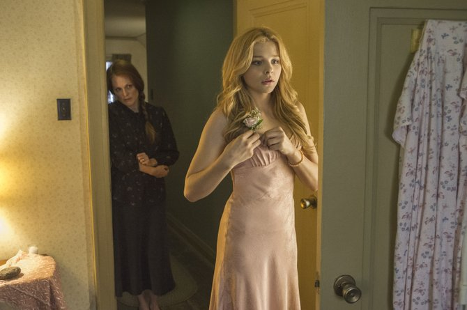 Carrie White (Chloë Grace Moretz) readies for the prom under the watchful eye of her mother (Julianne Moore). The movie is a remake of the 1976 film based on Stephen King's novel about a bullied teenage girl.