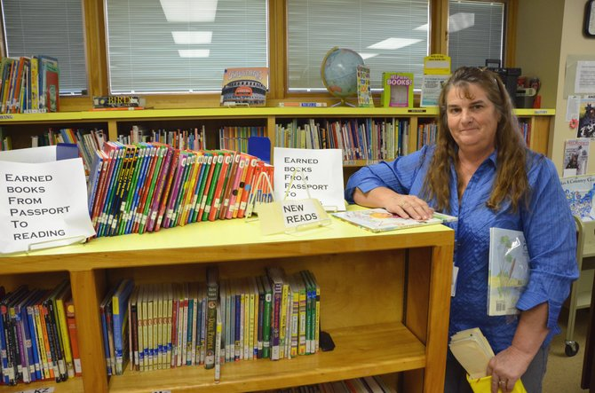 Cresh Wilson, Ridgeview Elementary School library and computer tech, displays the new books available in Ridgeview's library. Elementary school libraries around Craig received about 400 total new books though funding from local groups given for goals set during last year's Passport to Reading program.