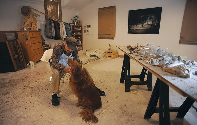 Gregory Block pets his dog Cayenne inside his Steamboat Springs studio. The studio also is his bedroom.