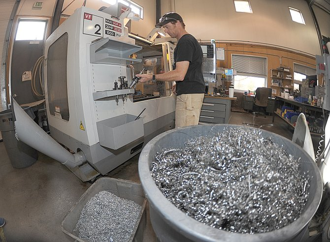 Eric Hindes, supervisor of the machine department at Moots, sets a machine up for its next task inside the Steamboat Springs factory. Moots collects shavings and small bits of material and takes them to Denver where they can be recycled. The company, which also recycles cardboard and any other materials that can be reused or recycled, was honored as the Steamboat Sustainable Business Consortium's Business of the Year. The Animal Healing Center, a local veterinary clinic, earned the Outstanding Achievement Award.