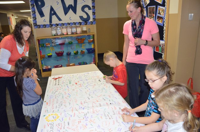 Ridgeview Elementary School Counselor Stacy Durham, left, and Desirae Pearcey, director of Grand Futures Prevention Coalition, assist Ridgeview students in signing a banner signifying their pledge to remain drug free. The banner is part of the National Red Ribbon Week program and can be viewed at American Family Insurance.