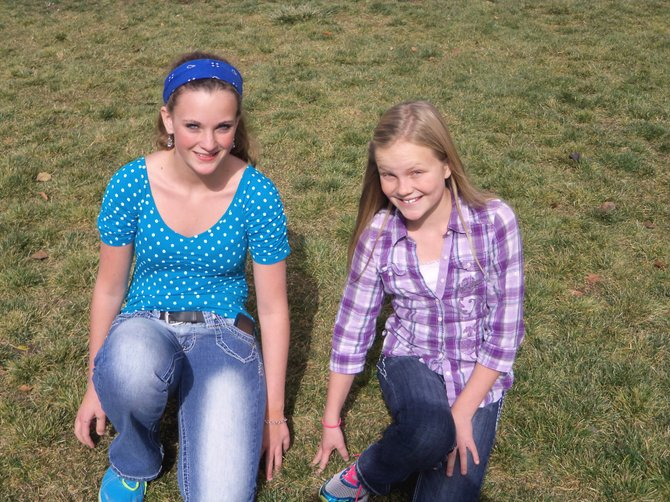 Craig Middle School seventh-graders Lacey Wiseman, left, and Caroline Riley kneel by what hopefully will be the site of an outdoor volleyball net within the next year. The two of them have raised more than $500 out of a goal of $2,000 to complete the project.