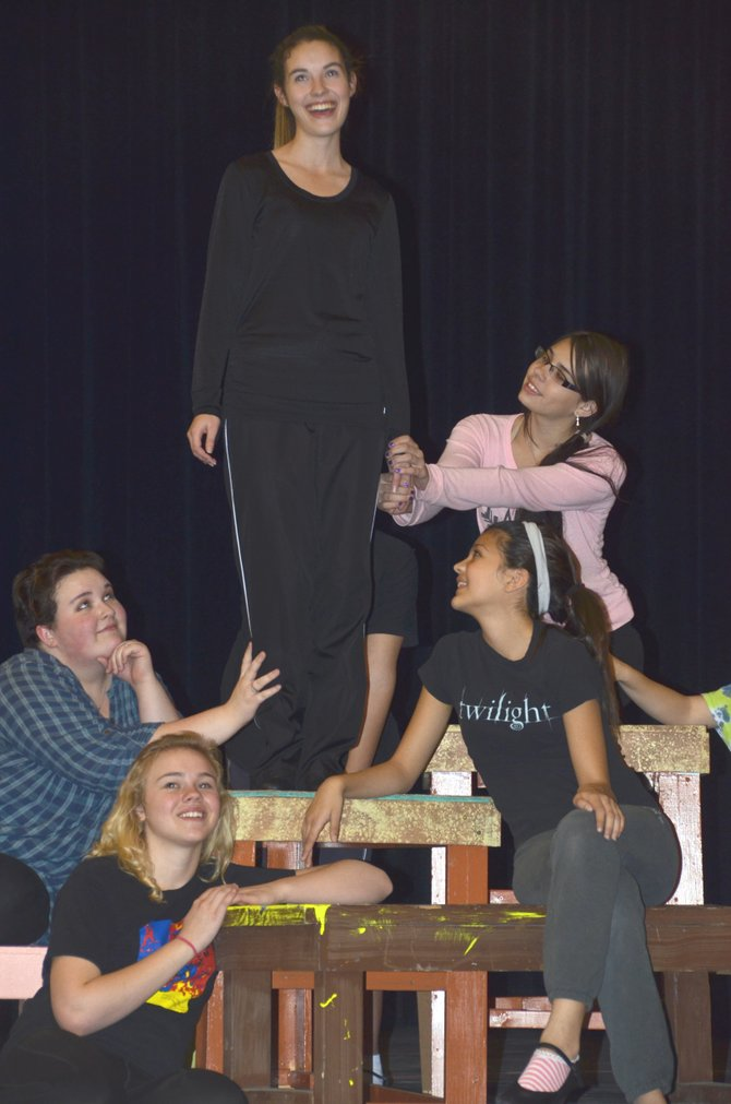 "The female students of Rydell High gather around Sandy, played by Moffat County High School senior Caitlin Harjes, as she sings  ""Summer Nights"" during a rehearsal for ""Grease."" The school's fall musical will feature performances Nov. 21, 22 and 23."