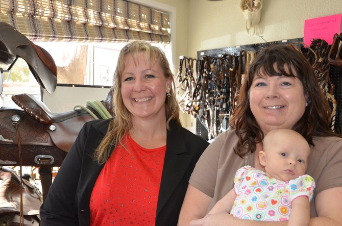 RaeAnne Hadley and Kim Zimmerman enjoy each other's company at Northwestern Tack in downtown Craig. Hadley sold the business to Zimmerman so she can focus on her oldest daughter's health. Zimmerman often gets to watch her 3-month-old granddaughter Arlea while she runs the store.