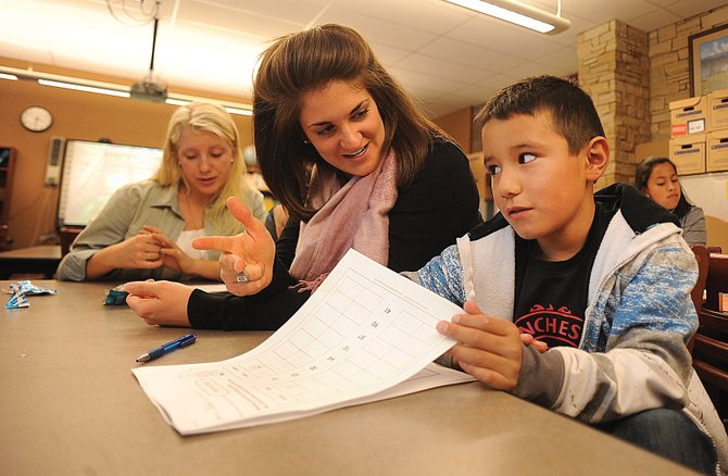 Third-grader Alexis Jimenez gets help from school-based mentor Becky Kruger on his math assignment during homework club at Soda Creek Elementary School. Kruger helps organize the program every Monday.