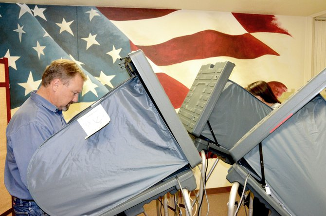 Mike Bailey, left, and Megan Cook vote at the polls Tuesday afternoon at Moffat County Courthouse.