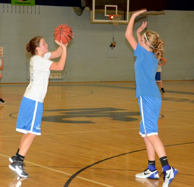 Lauren Samuelson, left, puts up a jumper over Mattie Jo Duzik Wednesday during an open gym at Moffat County High School. Many members of the girls basketball team started attending open gyms since the end of their fall sports seasons.