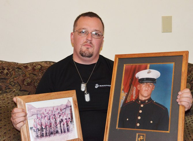 Hayden resident John Kregar holds a picture of his platoon from the Iraq war and his Marine photo. He suffers from post-traumatic stress disorder but found comfort and therapy in a poem he wrote about combat.