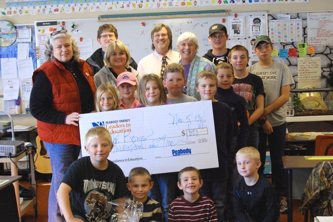 Maybell School teacher Bill Ronis is joined by his students while being presented with the Peabody Energy Leader in Education award, a check for $1,000, from Peabody representatives. Front row from left: Tanner Musser, Ben Yarmer, Kouper Rasmussen, Cactus Barnes; second row: Kydalin Phillips, Rielynn Hicks, Boudicea Higley, Cody Eckhoff, Ethan Schaaf, Ezra Phillips; third row: Maureen Moore, Lorena Schafer, Gayle Dudley, Lyric Davis; and back row: Scott Harrell, Bill Ronis, Colin Jensen and Colt Eckhoff.