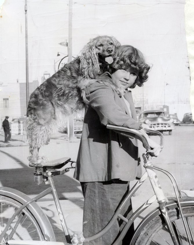Sally Terrill peers out from beneath her bangs as her dog, Taffy, balances on her shoulders.  Craig photographer Shorty Newell captured this image on a sunny Saturday afternoon in October of 1951, at the corner of Victory Way and Yampa Avenue.""