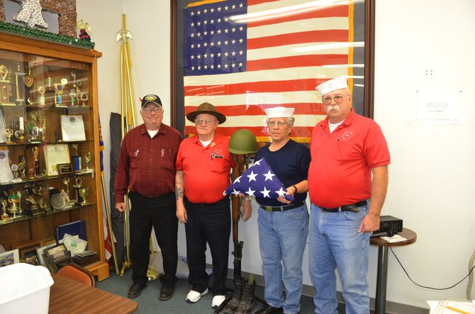 From left, Dave Walters, Jim Meineke, Bennie Otero and Mark Wick display the Veterans of Foreign Wars Post 4265 commemorative flag, a ceremonial flag and the Solider's Cross on Sunday morning at the VFW. The four of them are among the many veterans living in Craig and Moffat County who have fought for their country and are acknowledged as part of Veterans Day.