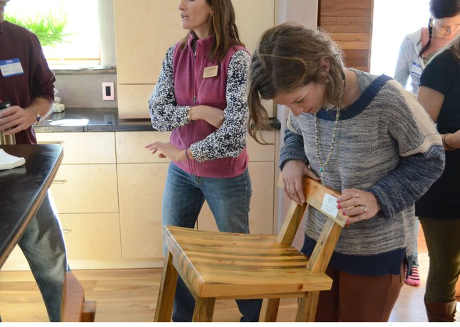 Colorado Mountain College student Caroline Jordan examines a chair inside Ron Davies' home during Sunday's Green Building Tour in Clark. Just about everything inside Davies' home, down to the chairs and countertops, were designed with energy efficiency and sustainability in mind.