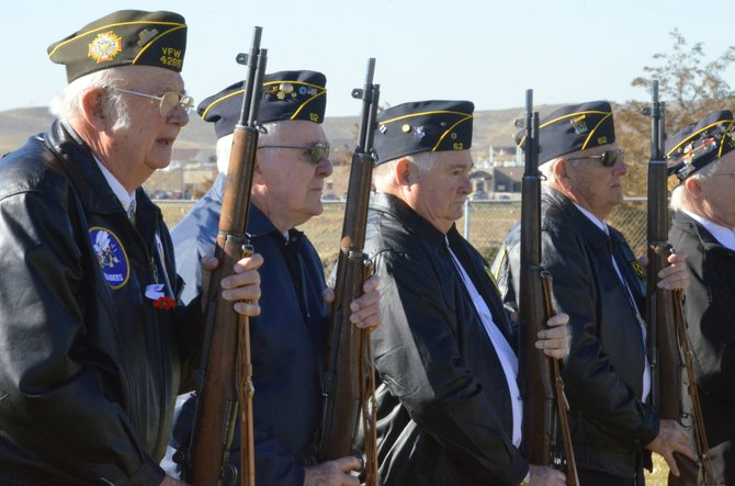 Members of the Honor Guard consisting of local veterans stay at attention following a 21-gun salute during Moffat County High School's Veterans Day assembly Monday morning. The event honored those who have served in the military.