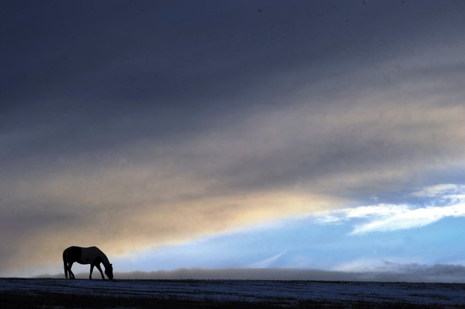 Storm clouds hover as a horse grazes on a ridgeline along Routt County Road 33 south of Steamboat Springs. The weather in Steamboat Springs is expected to change in the next few days as a series of storm fronts moves through the area.
