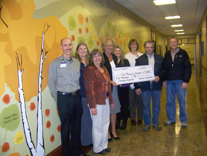 Todd Rose and Albert Bertagnolli, from right, of Questar Corporation, present a check for $5,000 to the members of The Memorial Hospital Foundation. The donation will be used to purchase software for the emergency department. Also pictured, from left, are Bryan Chalmers, Kristine Cooper, Eva Peroulis, Sue Lyster, Vicki Gallegos and Kim White.