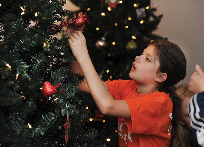 Emi Ramirez decorates a tree at the Tread of Pioneers Museum on Thursday for this year's Festival of Trees event. The annual fundraiser for the museum opens Saturday and will run through Nov. 25.
