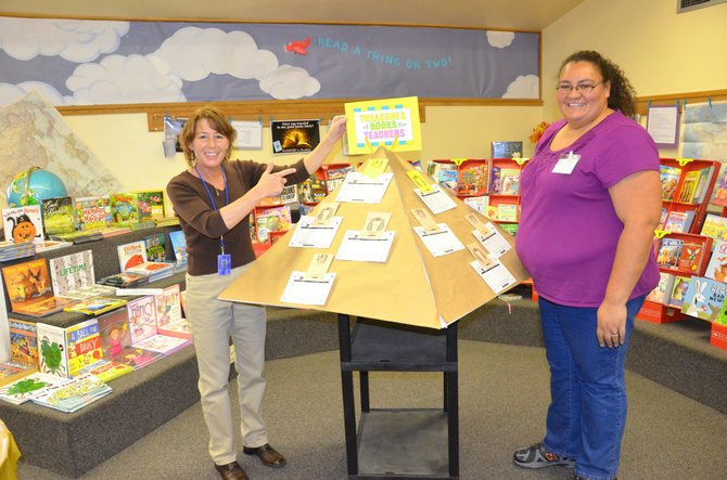 Librarian Tracey Hart, left, and Sunset Elementary School Advisory Committee member Tilila Gunderson display the pyramid containing teacher wish lists for the Scholastic Book Fair in the Sunset library. The fair will be available at Craig elementary schools this week.
