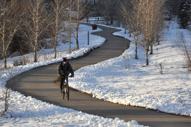 Tim McClenathan rides his bike on the Yampa River Core Trail on Monday evening.