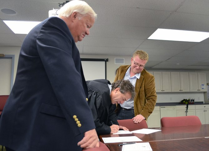 Judge Paul Sachs, middle, Roger Good, left, and Joey Andrew sign oaths of office Monday evening. Good and Andrew are the Steamboat Springs School Board's newest members.
