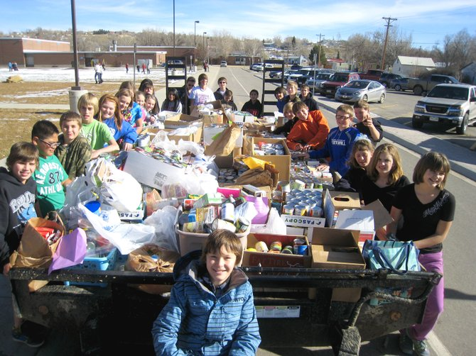 The students of Craig Middle School teachers Vicki Blomquist and Melissa Prestangen stand proudly by a flatbed loaded with donated food items. CMS collected roughly 3,400 pounds of food and raised more than $3,000 for the Interfaith Food Bank in the past month, donating the materials Monday.