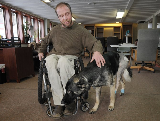 Ian Engle pets Zuma inside the Northwest Colorado Center for Independence, where Engle works. Zuma is in training to become a service dog and is on the road to recovery after being hit by a car Nov. 15.