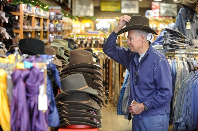 Steamboat Springs resident Ted Swain tries on a hat Friday while shopping at F.M. Light & Sons.