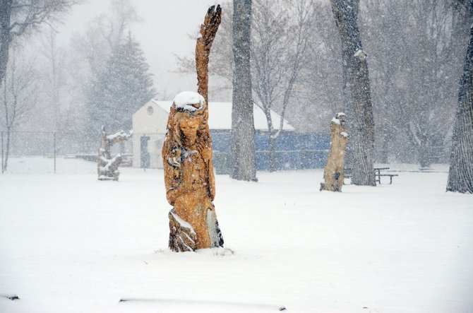 Snow covers the grass, trees and wood carvings Tuesday afternoon at Craig City Park. The National Weather Service predicts Craig will see about 4 to 8 inches of snow by Wednesday morning.