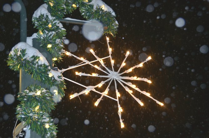 Snow swirls around a snowflake-shaped Christmas decoration hanging from a light post along Yampa Avenue in Craig.