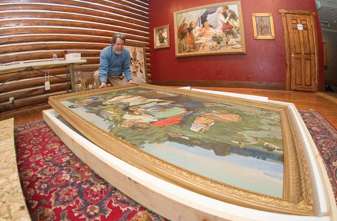 "Show curator Richard Galusha upacks one of the large paintings that will be on display during a show called ""The Russian Experience."""