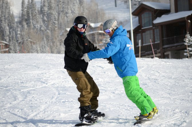 Sometimes, it takes a helping hand to get down the mountain when you're a beginner snowboarder. Frustration can settle in for the learner, but a patient instructor like Danny Pinegar, right, can make all the difference.