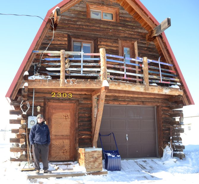 "Bill Sawer stands in front of his self-built log cabin on the west side of Craig. ""Soccer Bill"" has lived in the Yampa Valley for over 40 years and has been a major part of the skiing and soccer communities in Steamboat and Craig."