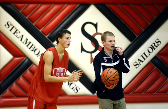 Steamboat Springs High School boys basketball coach Luke DeWolfe hands the ball into play Wednesday during the team's last practice before the Steamboat Springs Shoot-Out basketball tournament begins Thursday.