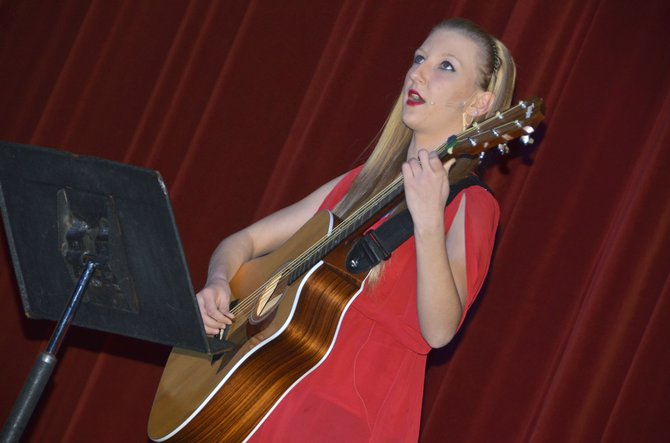 "Moffat County High School sophomore Paige Durbin strums and sings Kelly Clarkson's ""Irvine"" during the second annual Kennel Club Talent Show on Thursday evening at MCHS. The night featured performances from a number of students, as well as faculty member Lindsay Smith, and raised funds for the Make-a-Wish Foundation."