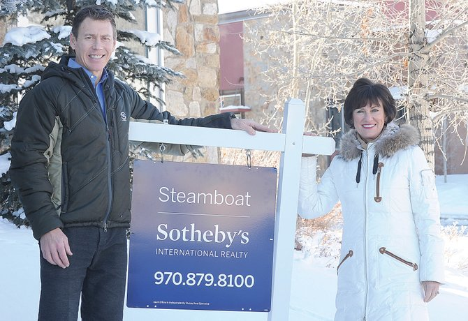 Cam Boyd and Pam Vanatta stand next to a sign for Steamboat Sotheby's International Realty. On Jan. 2, Boyd and Vanatta's Prudential Steamboat Realty will transition to the Sotheby's International Realty brand.