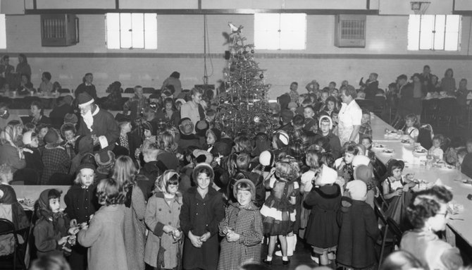 Children mill around in the Breeze School gymnasium at the 1953 school Christmas party. Complete with Santa, gifts and a full meal, the party was a tradition that continues on today in our local schools.