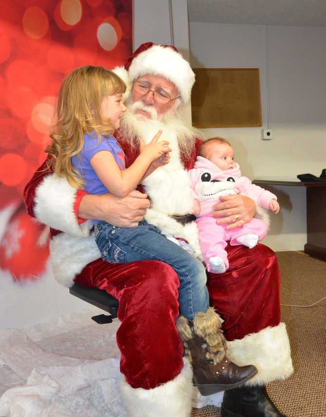 Abby Turner, left, talks to Santa Claus about some of the things she wants for Christmas this year, while her younger sister Reagan hangs out at Letters to Santa at the Craig Daily Press offices. Hundreds of children came to drop off their letters for Santa, as well as visit and take pictures.