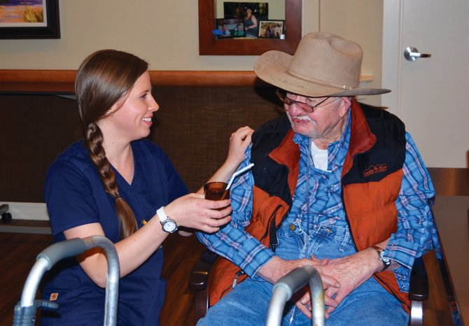 Certified nursing assistant Laura Steinke offers Doak Walker House resident Larry Puryear a glass of juice at the end of an all-night shift Wednesday morning.