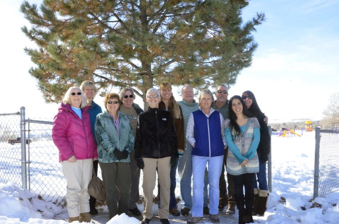 Former employees of East Elementary Schol assemble at the northeast corner of the school's playground in front of a tree donated by former principal Jim Covalt. Covalt, who died Nov. 26 in Colorado Springs, donated the tree to the school upon his retirement in 1990 after 23 years in Moffat County. Pictured are back row from left, Sue Goodenow, Joyce Phillips, Michelle Foulk, Oliver Phillips, Brett Sperl and Janele Husband. Front row, from left, are Peggy Bomba, Theresa Moyer, Robin Weible, Vicky Hughes and East alumnus Isis Beckett.