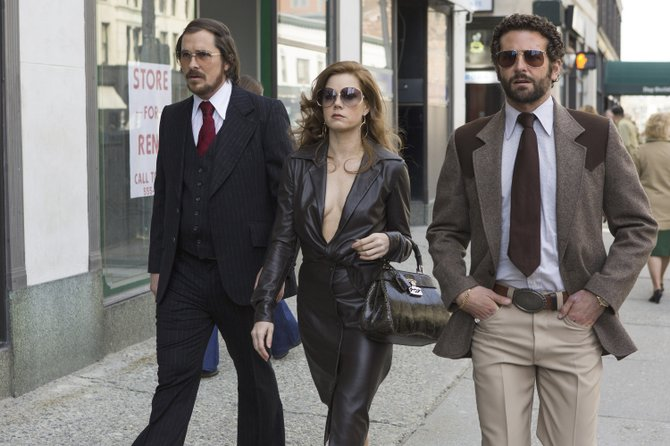 "Irving Rosenfeld (Christian Bale), Sydney Prosser (Amy Adams) and Richie DiMaso (Bradley Cooper) prepare for a sting operation in ""American Hustle."" The movie is about a pair of con artists forced into helping the FBI pull off the Abscam operations of the late 1970s."