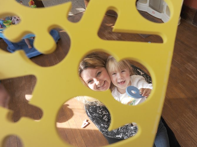 Katina Kline plays with 4-year-old Madison Fleeman on Thursday morning inside Katina's Wee Care Center. Katina recently opened the in-home day care center focused on taking care of toddlers.