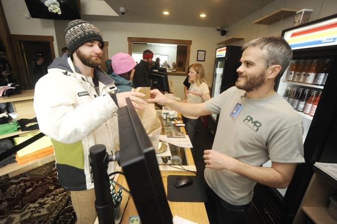"Rocky Mountain Remedies employee Chris Fisher hands over the first legal sale of recreational marijuana to Minnesota resident Patrick Krenke on Wednesday morning. Krenke spent $112.55 and paid for it using plastic. ""That's the first time I've bought weed without cash,"" he said."