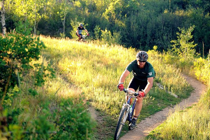 Matthew Doro rides through a sunlit meadow on Emerald Mountain during a Quarry Mountain Town Challenge race in Steamboat Springs. The city has appointed the first steering committee to help oversee funding of trails projects.