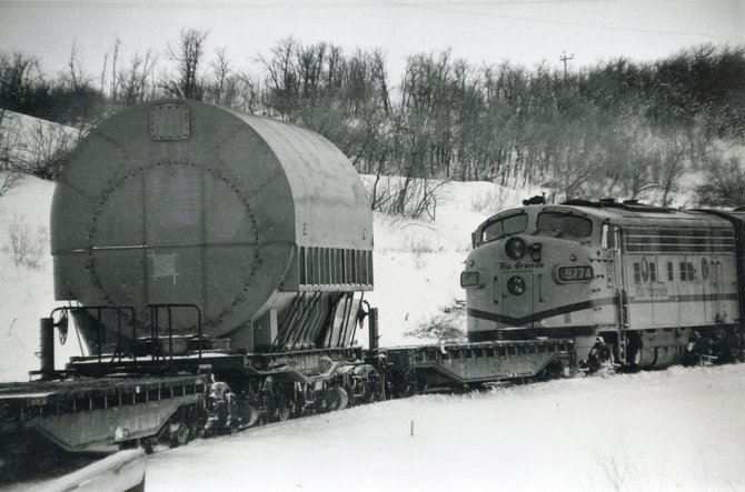 Denver & Rio Grande engine # 9774 inches the mammoth generator ponderously forward past snowy fields, on the last leg of its journey from Pennsylvania to the Hayden power plant site 50 years ago this month.