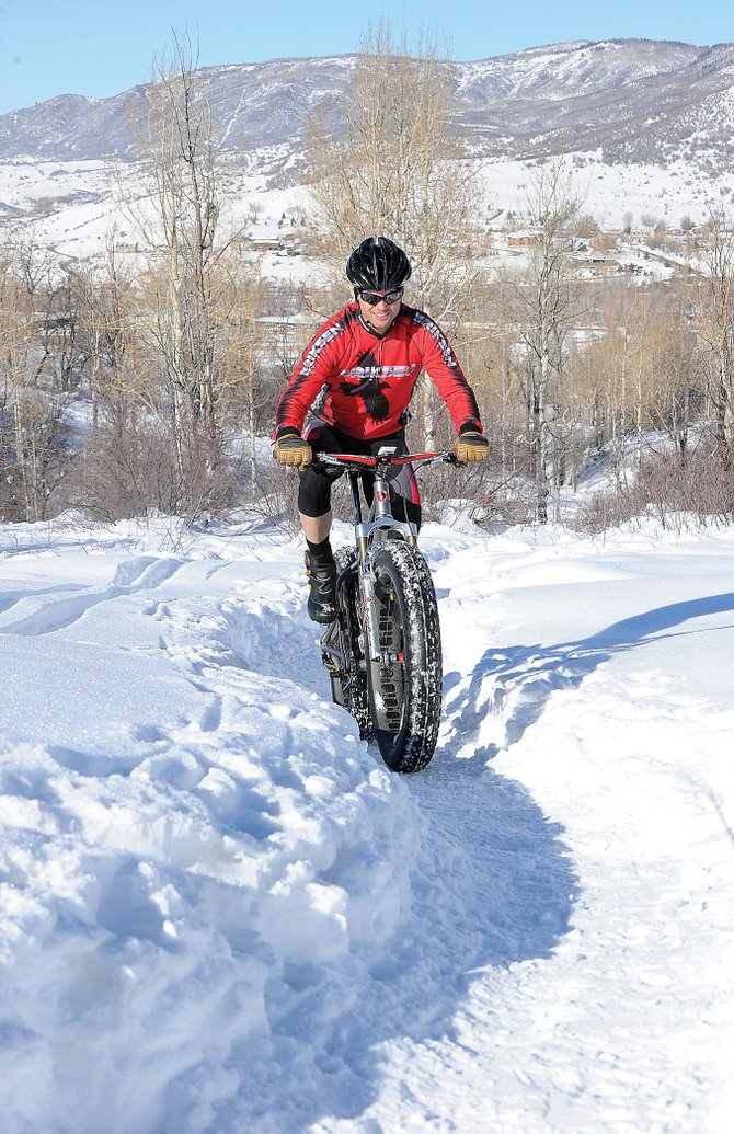 Cyclist Brad Bingham powers a trail on Emerald Mountain on a blue-sky day earlier this week. Bingham, who works for Eriksen bikes, said he has seen an increased demand for fat bikes as the sport continues to grow.