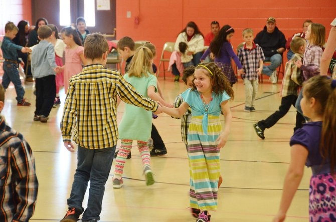 First-grader Iesha Martinez, center right, do-si-dos with dance partner Jerik Felten on Thursday afternoon during Sunset Elementary School's daylong dance program. Students in every grade spent the past two weeks learning square dance steps as well as dances from across the world.