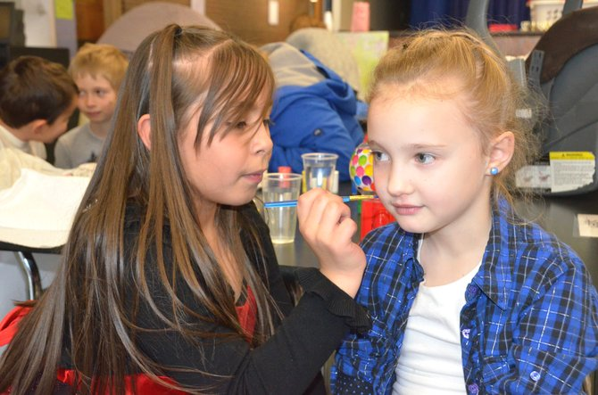 Sandrock Elementary School student Alondra Rodriguez, left, paints a pink heart on the cheek of Briley Nielson during the school's Economics Carnival Thursday afternoon. Sandrock's second grade classes used what they learned in their curriculum about money, goods and services and supply and demand to create a variety of game and food booths in the school cafetorium where they could set prices and work to provide customer satisfaction to classmates, parents and teachers.